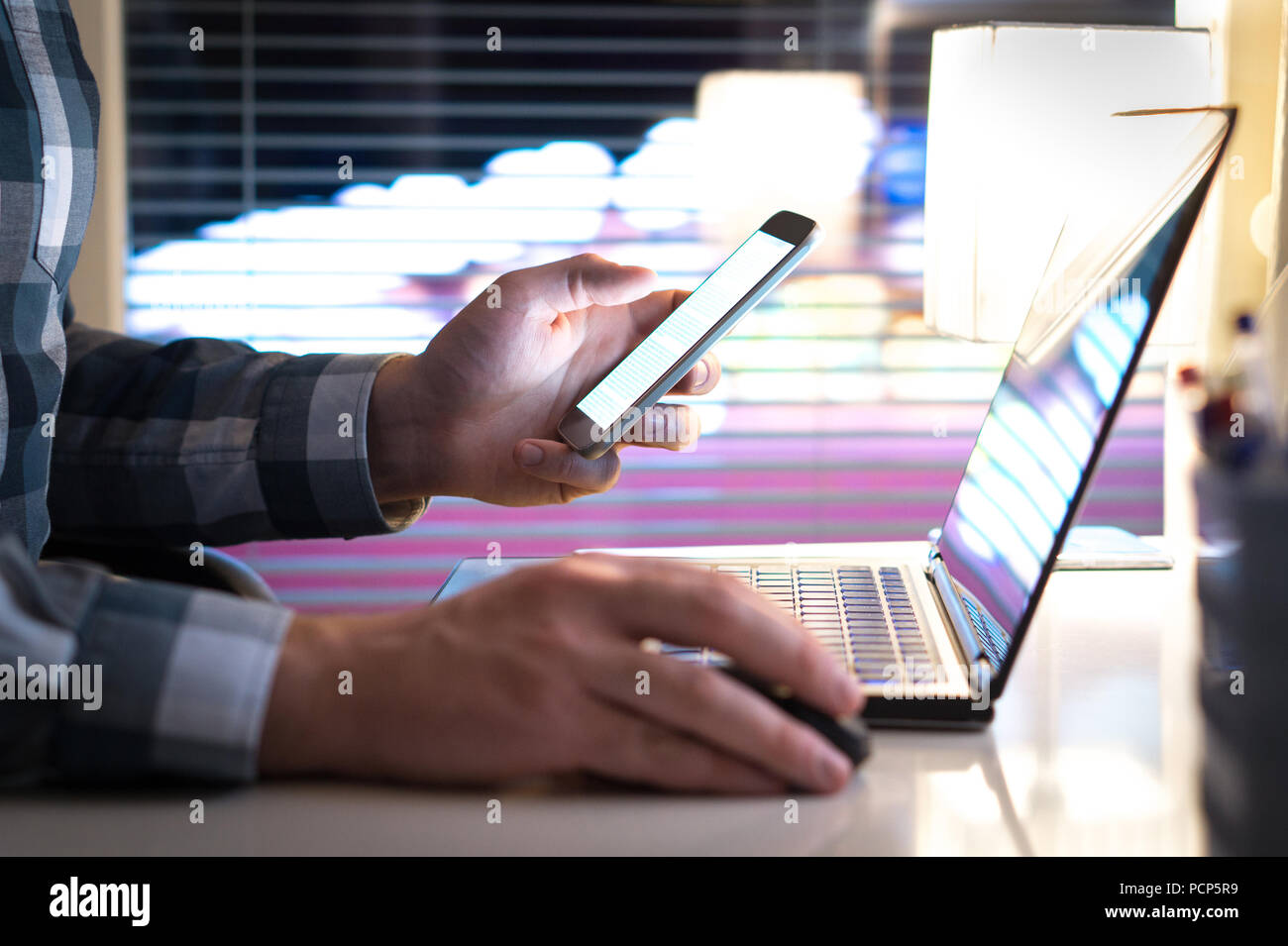 Man using smartphone and laptop late at night. Entrepreneur or businessman in modern work office. City lights in the background. - Stock Image