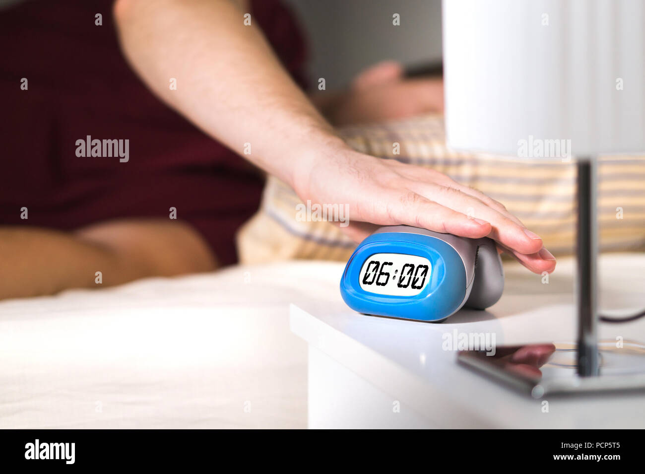 Man waking up in bed. Turning off alarm clock on nightstand or pressing snooze. - Stock Image