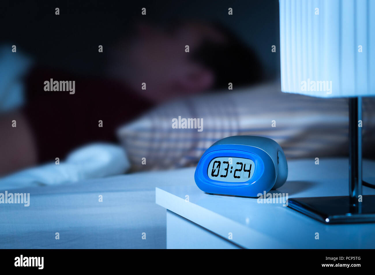 Close Up To Digital Alarm Clock On Nightstand In Bedroom. Man Sleeping In  Bed In The Background. Dreamy Blur Effect.