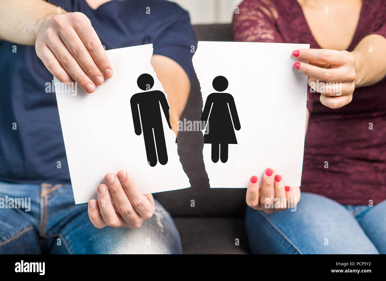 Break up, divorce and marital problems concept. Couple holding ripped pieces of paper with man and woman symbol. - Stock Image