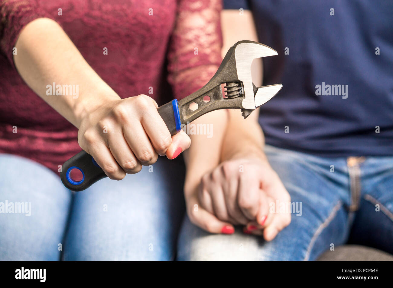 Fixing relationship problems concept. Couple holding hands in therapy and counselling session. Woman or wife showing a tool and wrench. - Stock Image