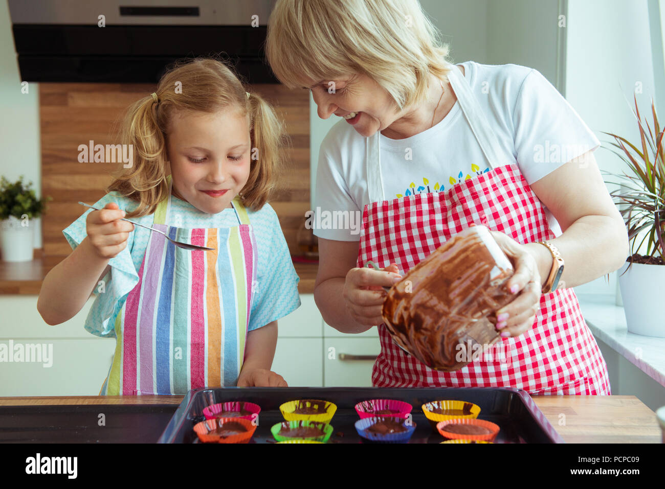Portrait of happy beautiful grandmother and her granddaughter in modern kitchen - Stock Image
