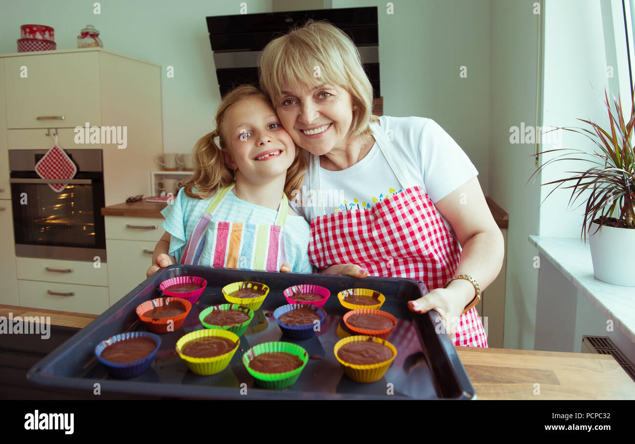 Portrait of happy beautiful grandmother and her grandchildren in modern kitchen have fun during baking - Stock Image