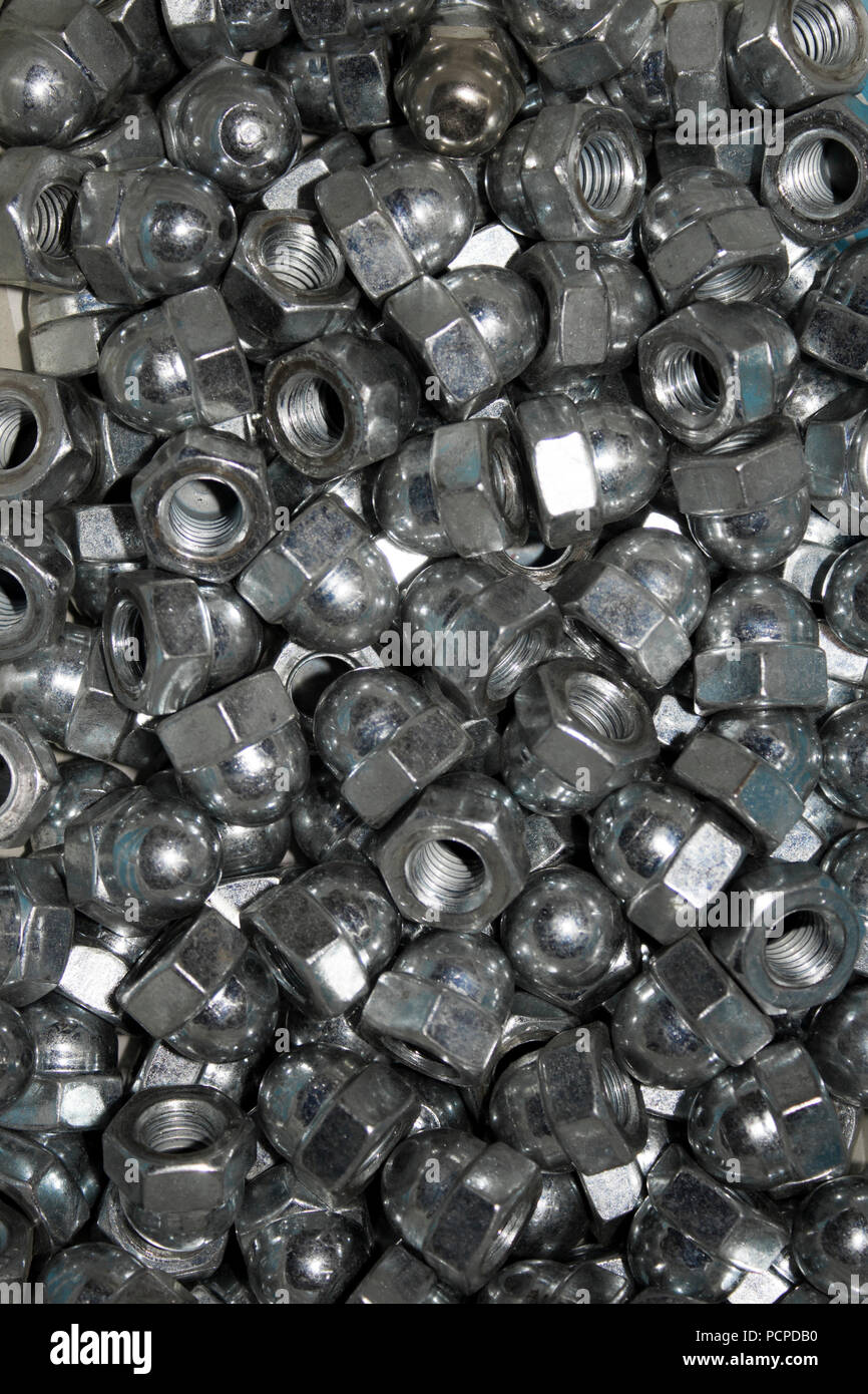 Lots of galvanized industrial steel cap nuts on a white background - Stock Image