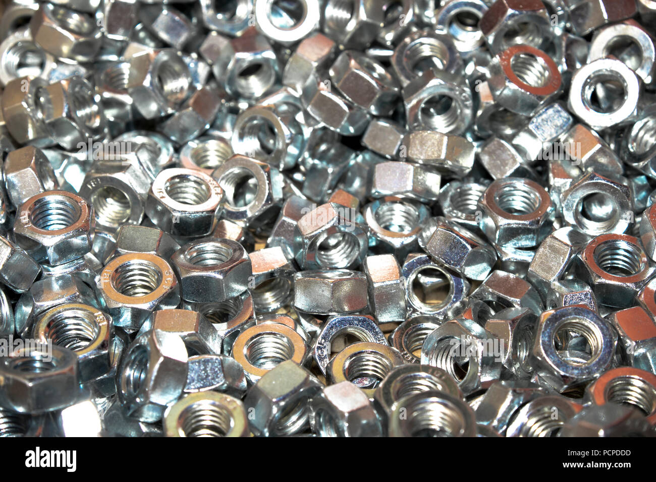 Lots of industrial galvanized steel nuts on a a big pile in warm light - Stock Image