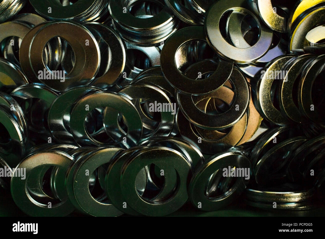 Pile of galvanized steel washers reflecting different colors in the sun light - Stock Image