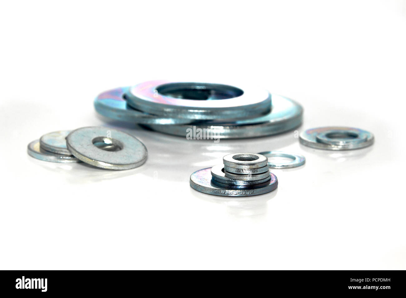 Variety of industrial galvanized steel washers on white background - Stock Image