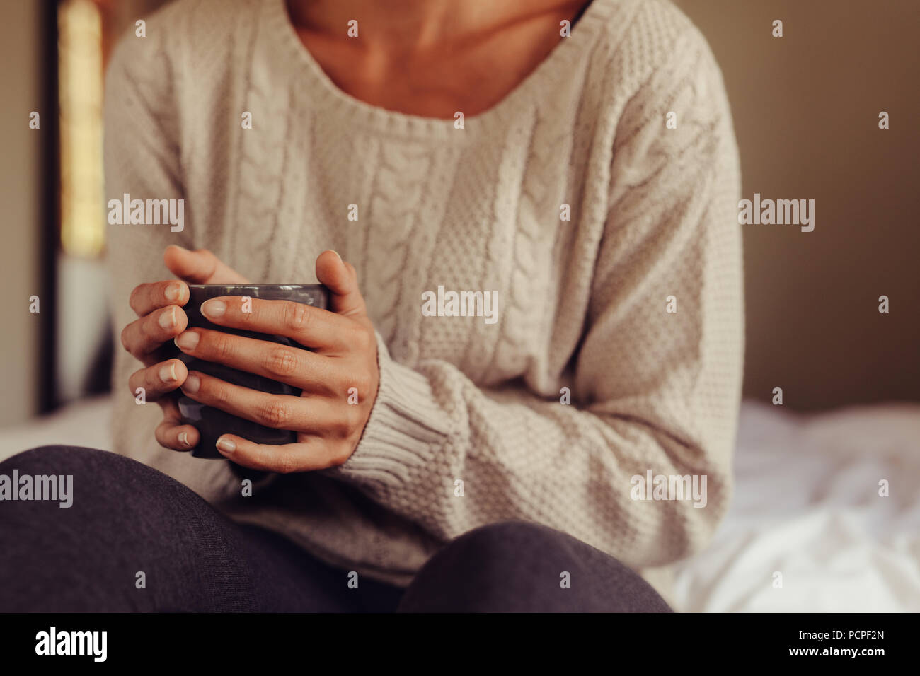 Close up of woman wearing sweater holding a cup of coffee while sitting on bed. Cropped shot of woman having morning coffee in bed. Focus on hands hol - Stock Image