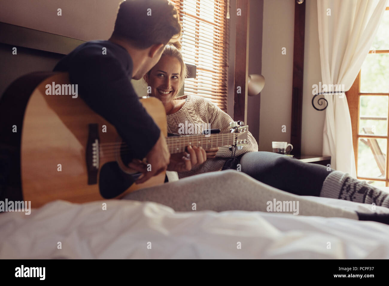 Young man playing guitar for his girlfriend in bed. Loving couple resting in hotel room and playing guitar in bed. - Stock Image