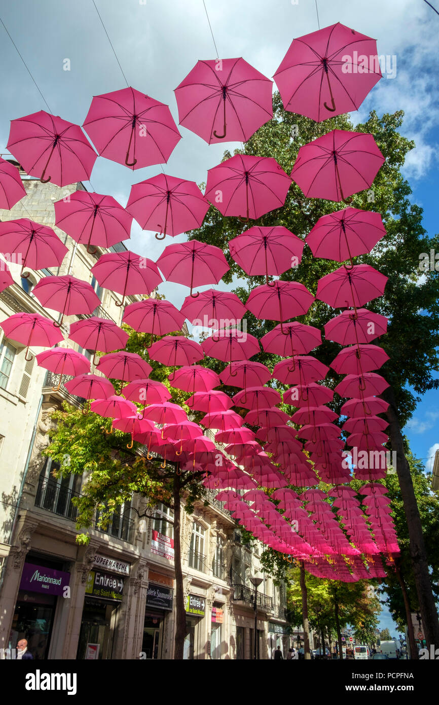 Saumur, France - 6th October 2017:  Pink umbrella art installation on a beautiful sunny autumn afternoon in Saumur, Maine et Loire, France - Stock Image