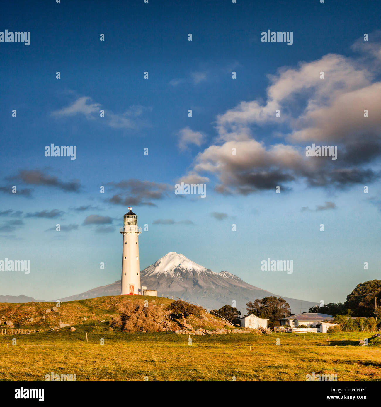 Mount Taranaki, also known as Mount Egmont, and Cape Egmont Lighthouse, Taranaki, New Zealand, at sunset. Stock Photo