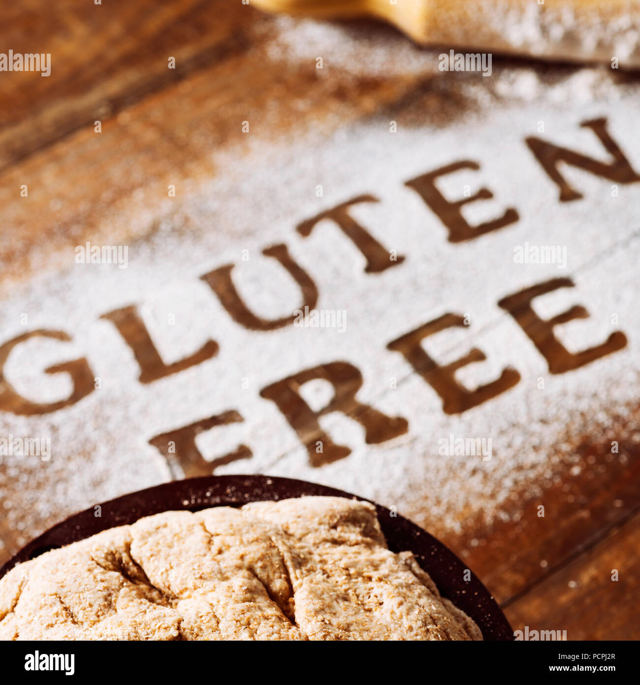 closeup of a wooden table sprinkled with a gluten free flour where you can read the text gluten free, next to a rolling pin and a piece of dough - Stock Image
