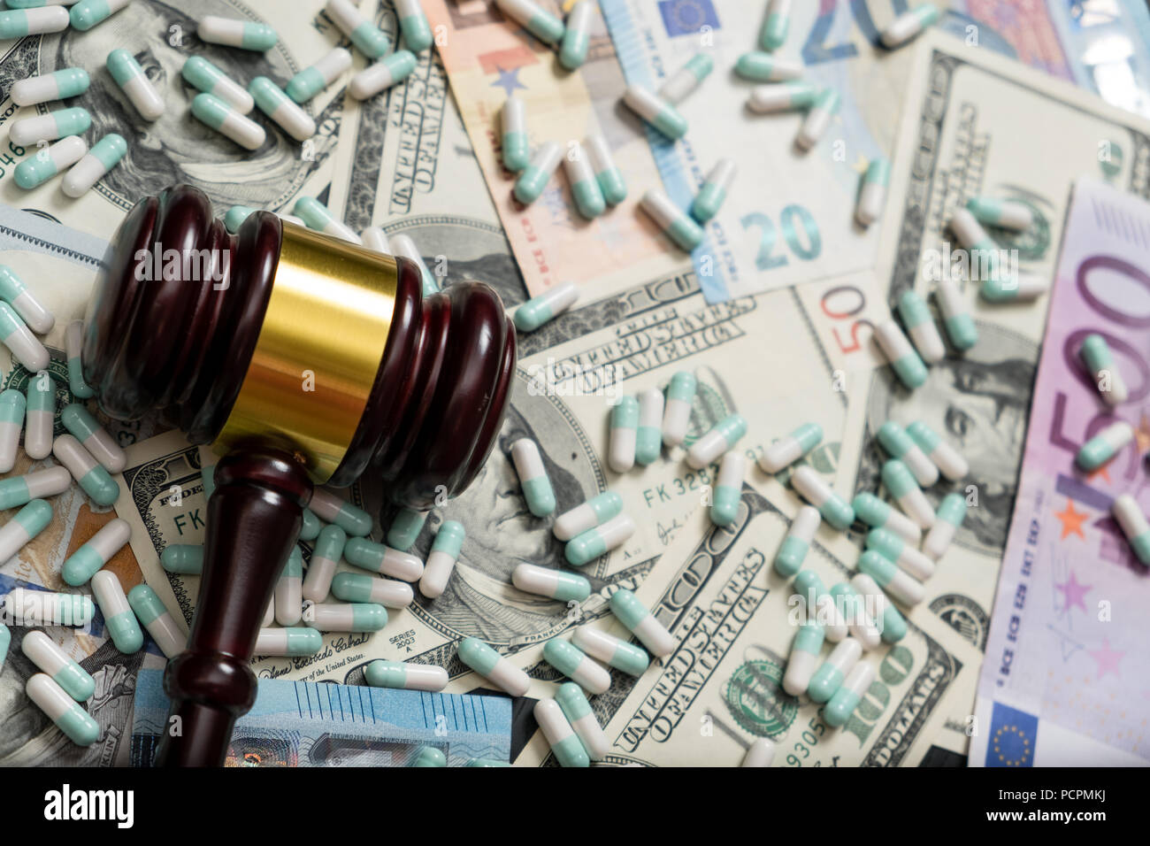 Wood judge's gavel and scattered colorful drugs on the dollar and euro cash background, drugs falsification, concept for medical negligence, bail. Ove - Stock Image