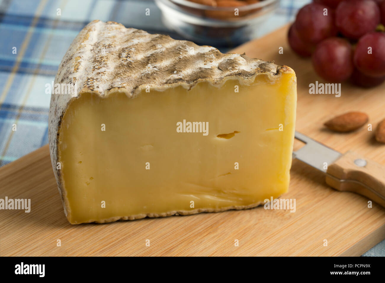 French Tomme de Montagne cheese on a cutting board as dessert - Stock Image
