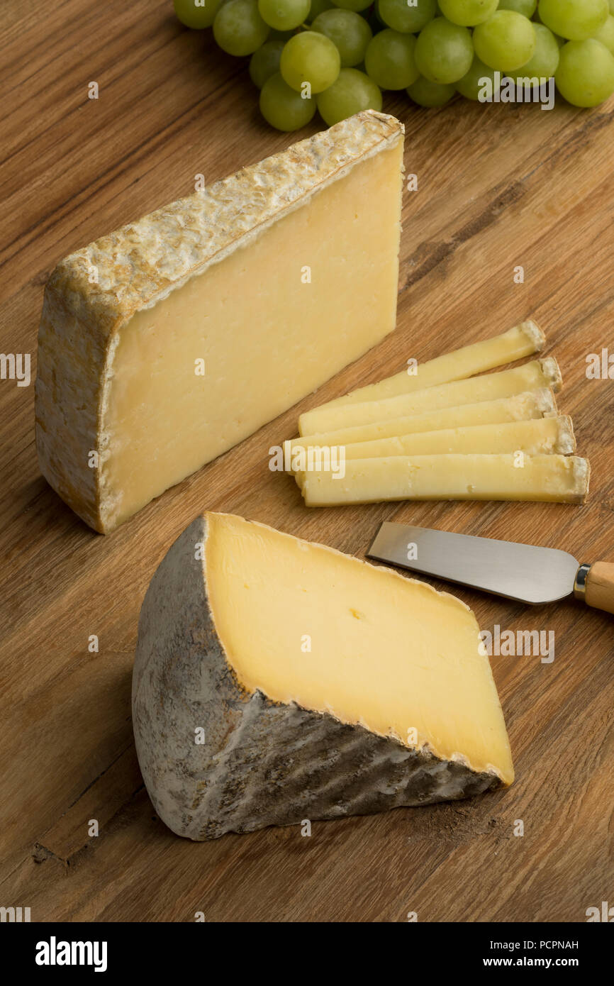 French Tomme de Montagne and Cantal cheese on a cutting board as dessert - Stock Image