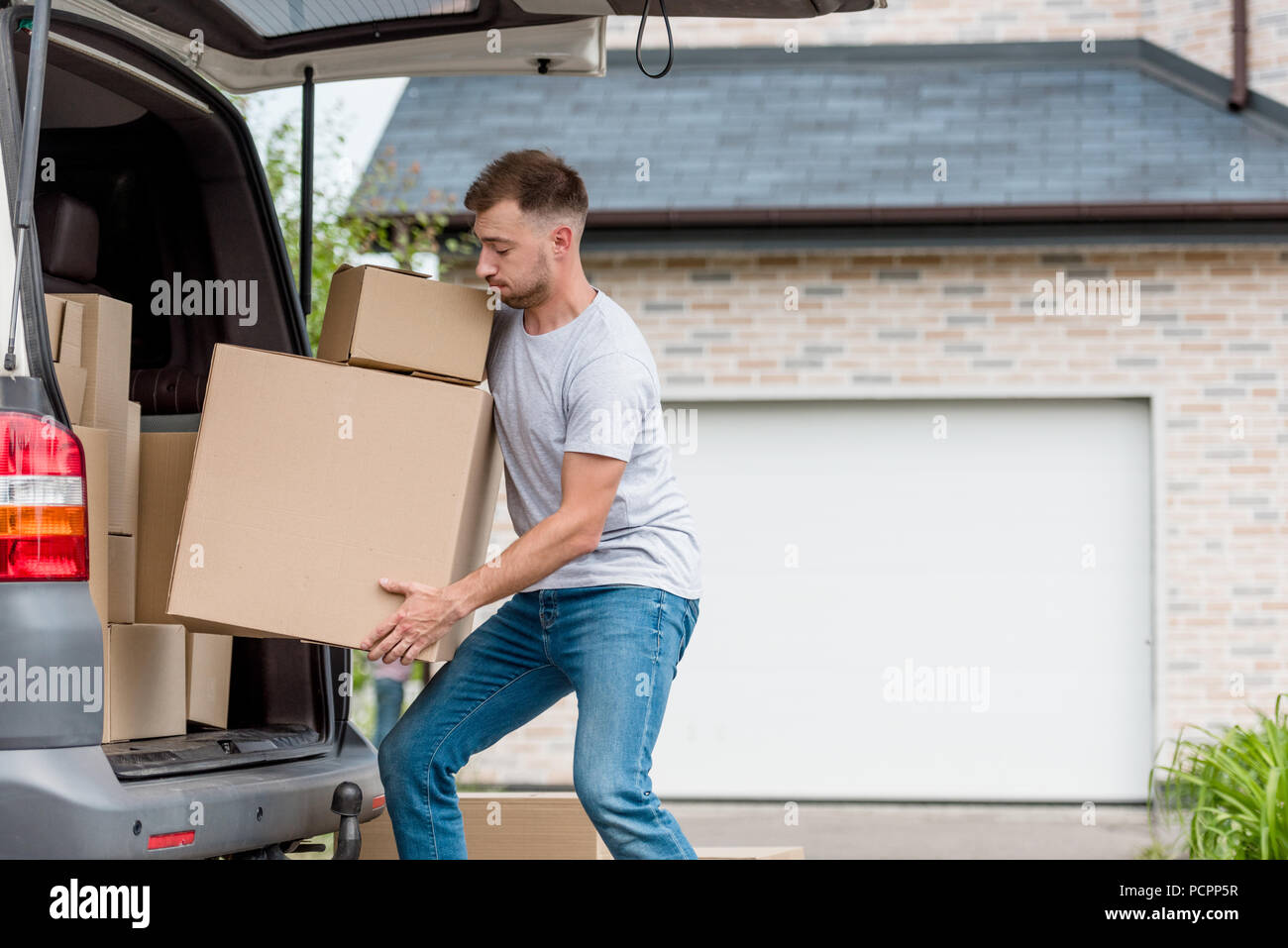 strenuous young man moving boxes from car into new house - Stock Image