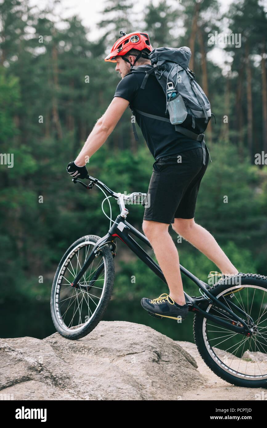 handsome trial biker balancing on rock outdoors - Stock Image