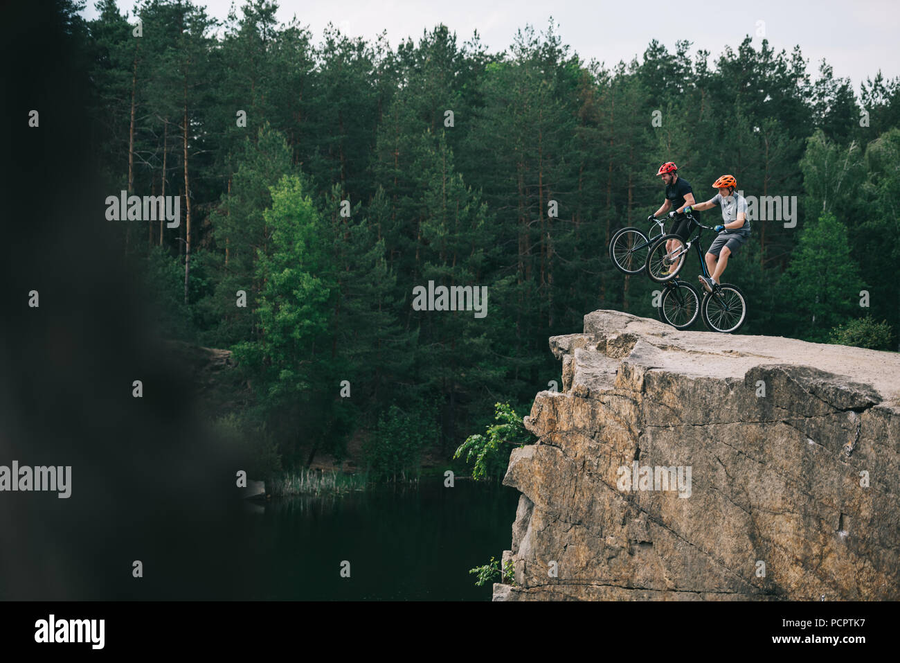 side view of extreme trial bikers standing on back wheels on rocky cliff with blurred pine forest on background Stock Photo