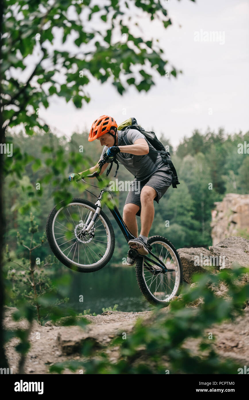 young trial biker performing stunt outdoors in front of forest lake - Stock Image
