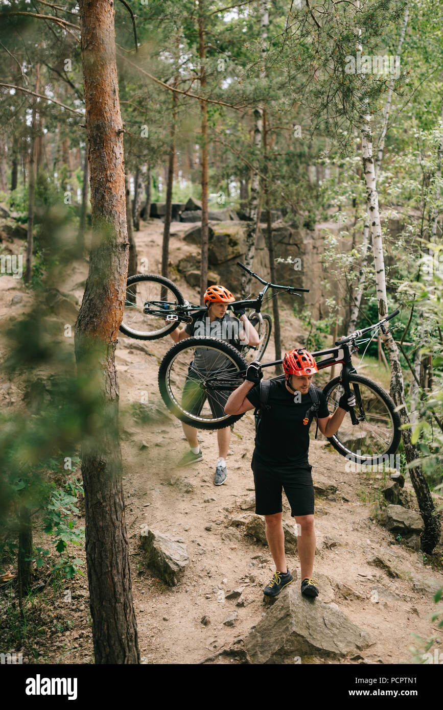 young trial bikers carrying bikes on backs at forest - Stock Image