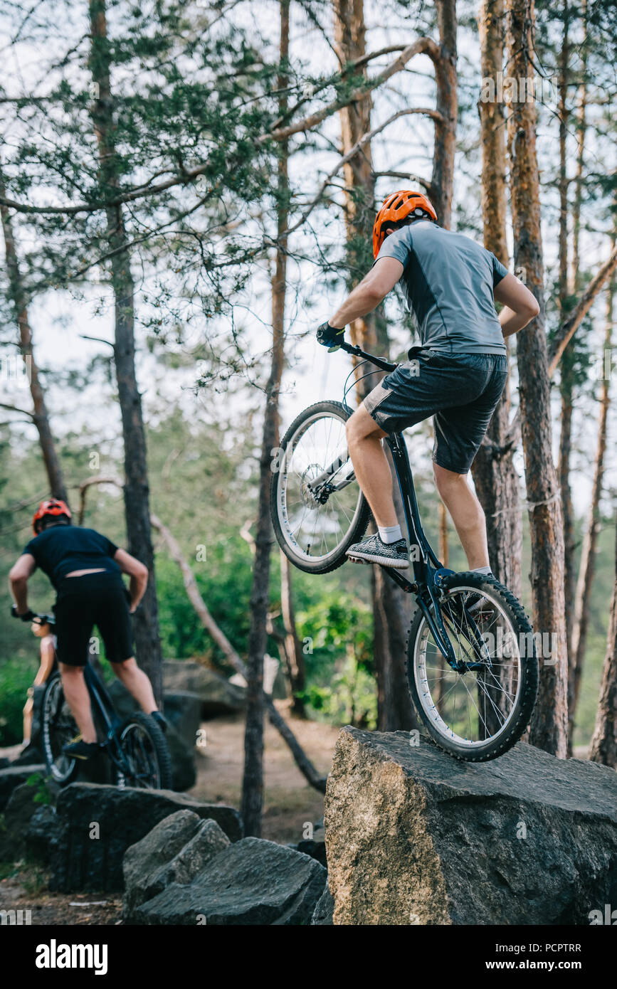 athletic young trial bikers performing stunts on boulders - Stock Image