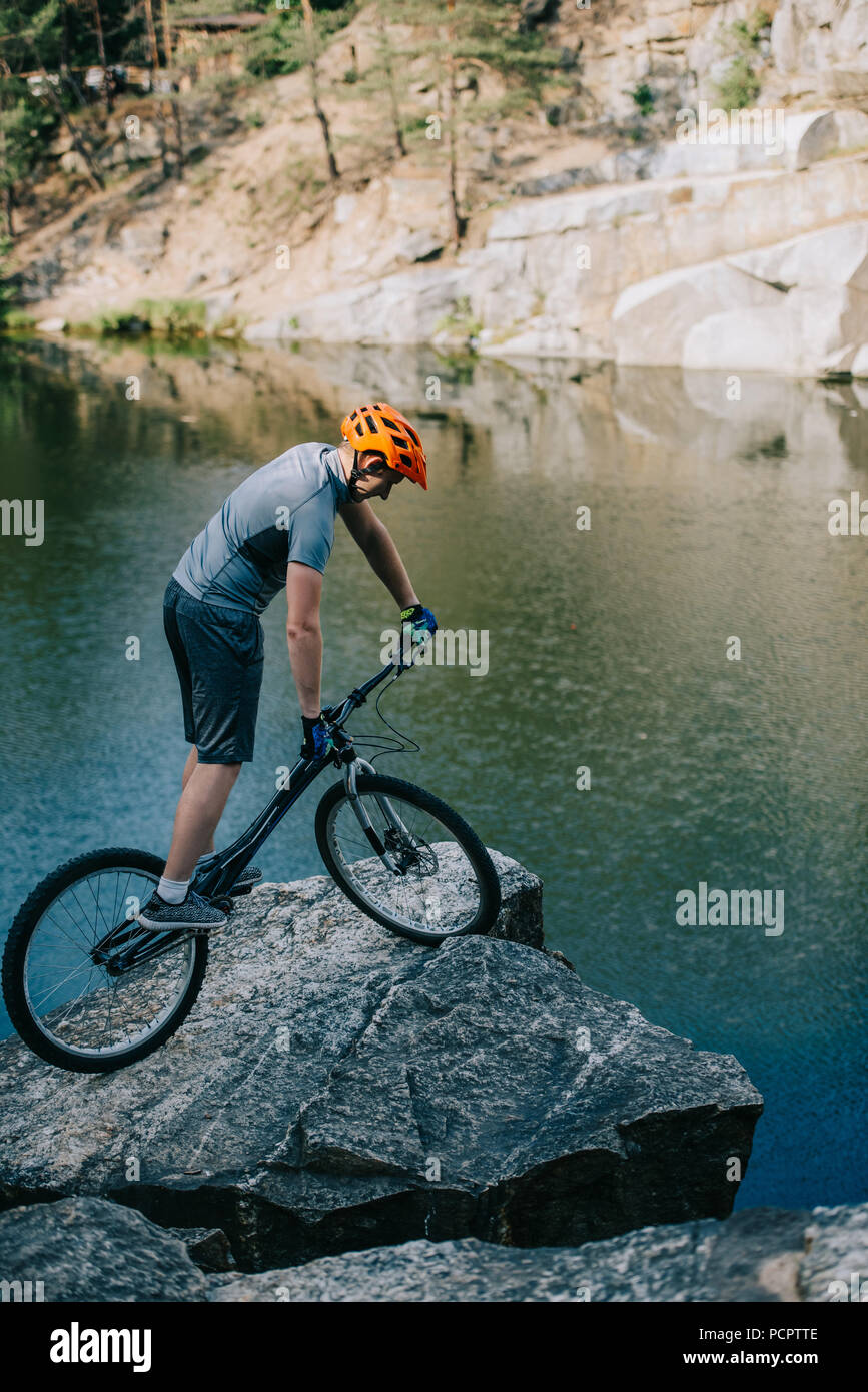 athletic trial biker balancing on rocky cliff over lake - Stock Image