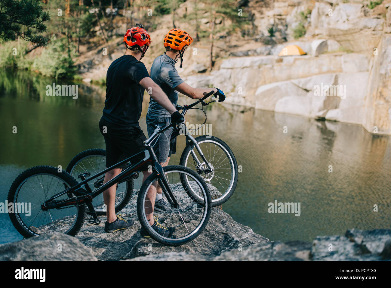 extreme trial bikers standing on rocky cliff in front of mountain lake - Stock Image