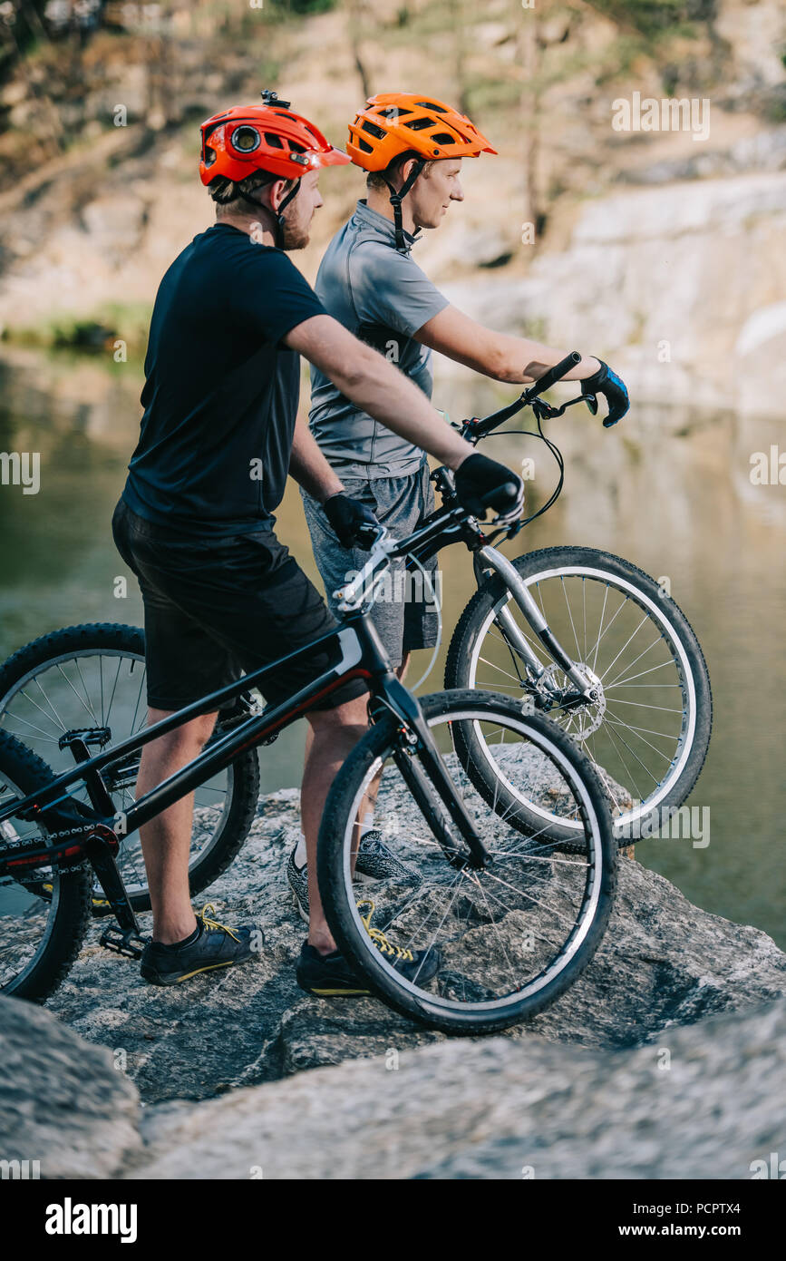 young trial bikers standing on rocky cliff in front of mountain lake and looking away - Stock Image