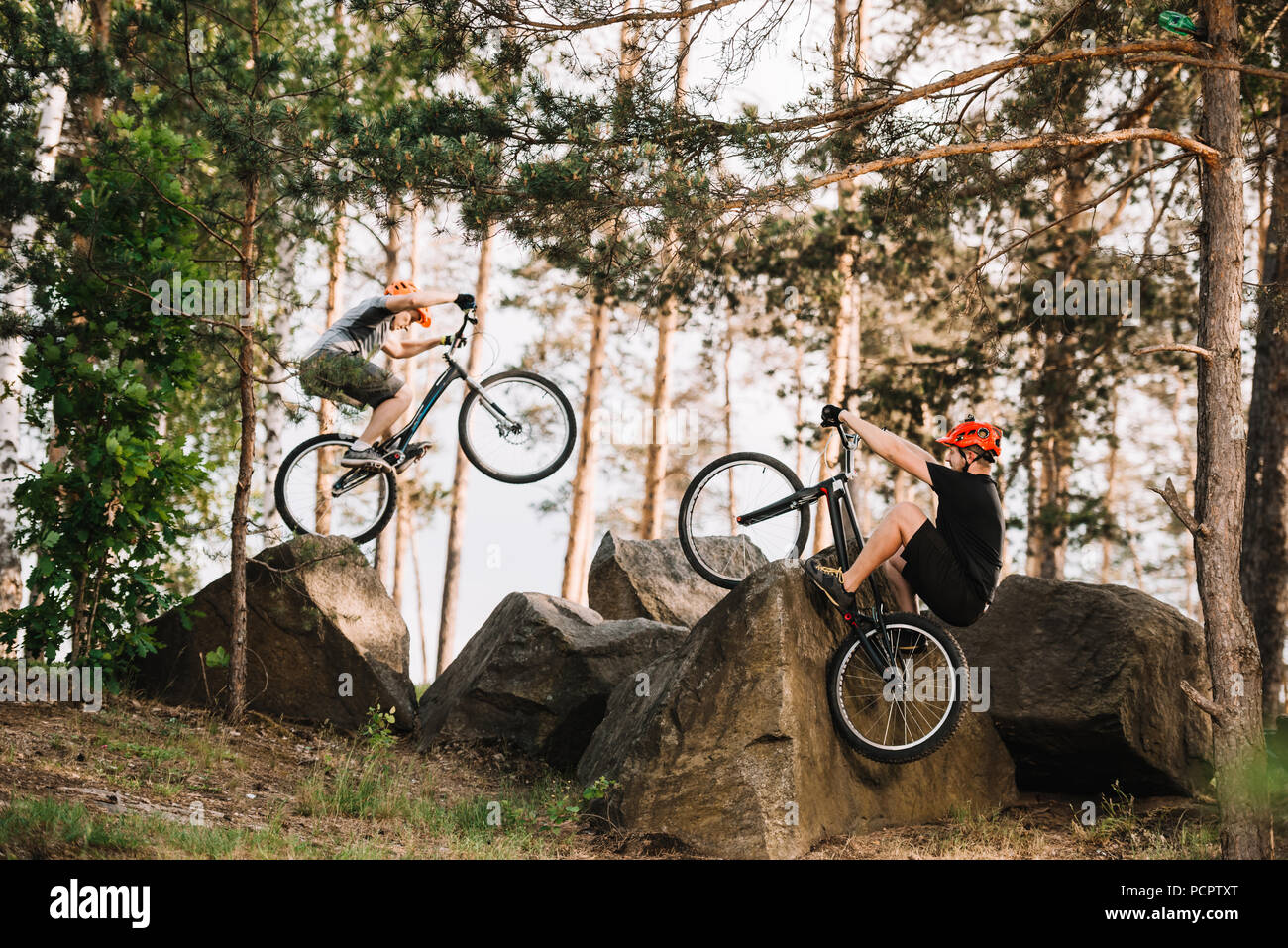 active trial bikers performing stunts on rocks outdoors - Stock Image