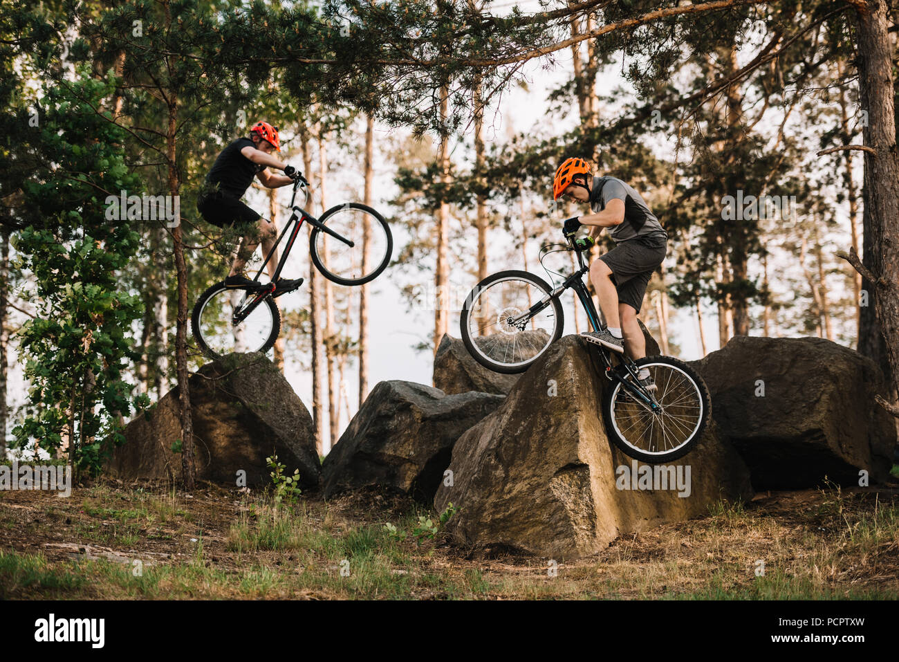 extreme trial bikers performing stunts on rocks outdoors Stock Photo
