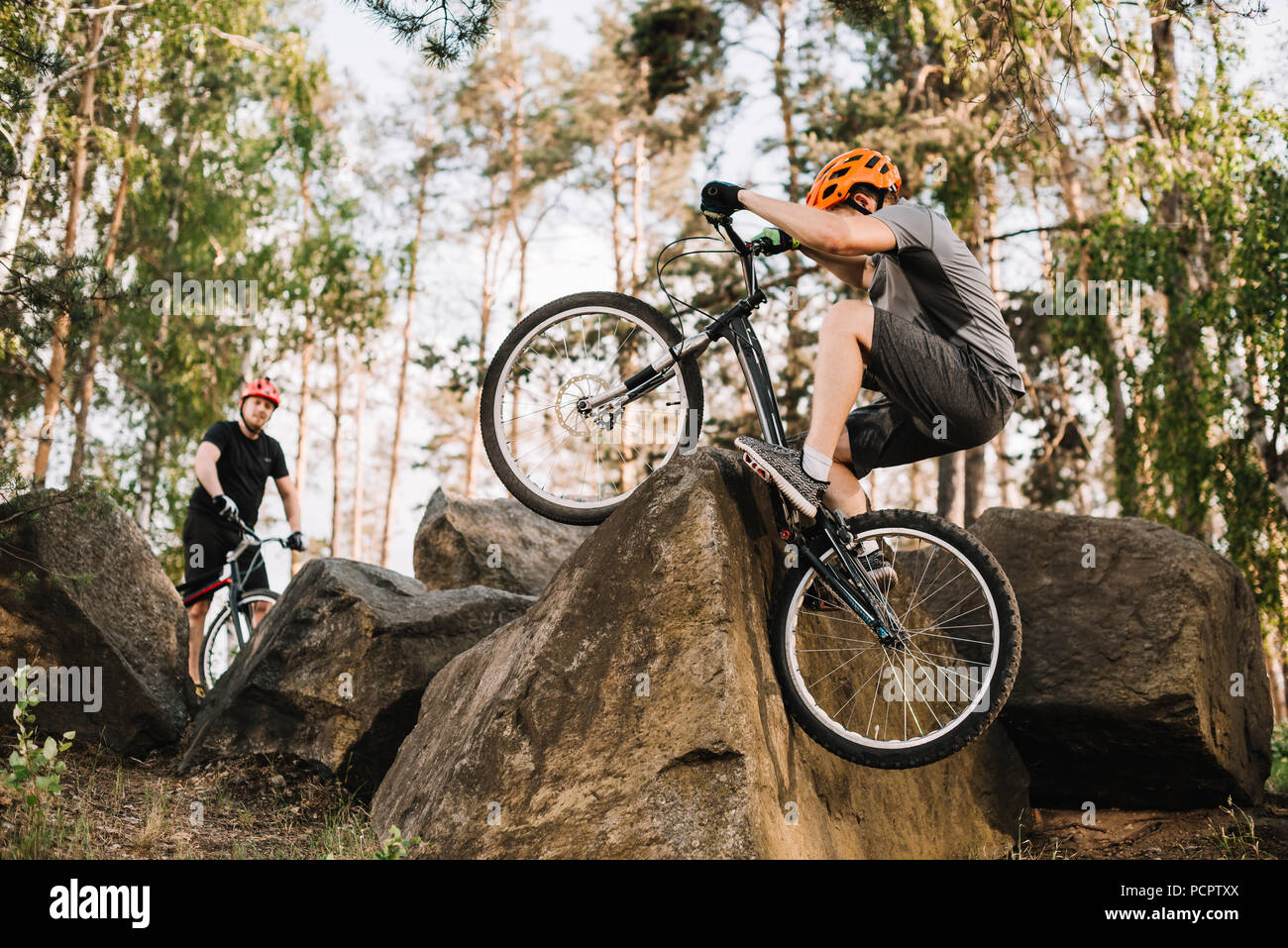 extreme trial bikers riding on rocks outdoors - Stock Image