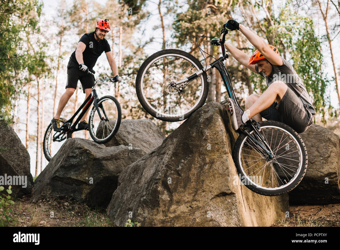 active young trial bikers riding on rocks outdoors - Stock Image