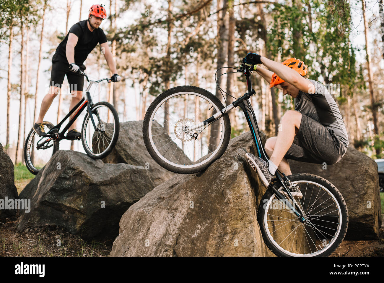 athletic young trial bikers riding on rocks outdoors - Stock Image