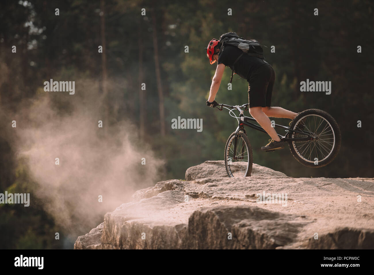 young trial biker balancing on front wheel on rocks outdoors - Stock Image