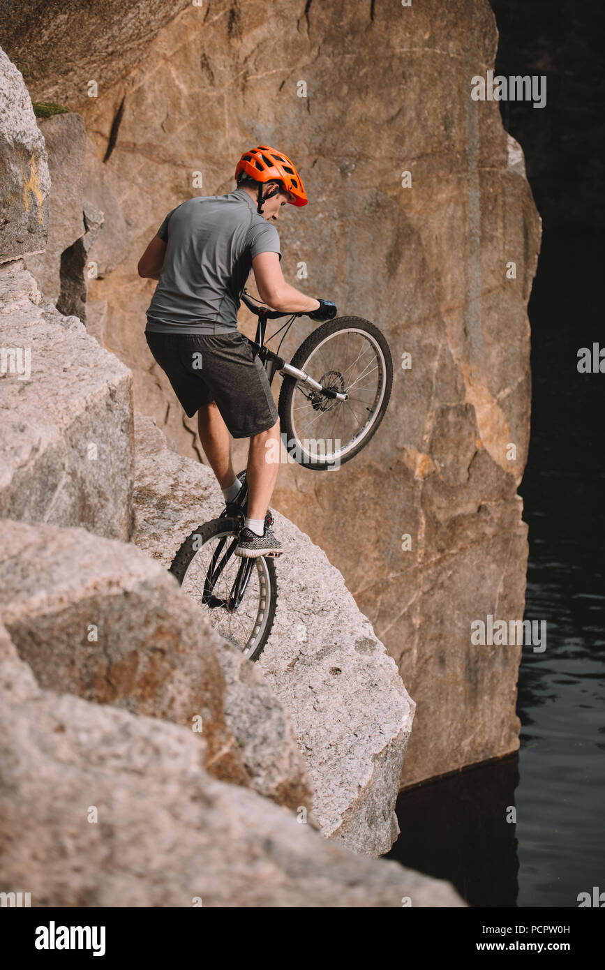 high angle view of trial biker balancing on back wheel on rocks outdoors Stock Photo