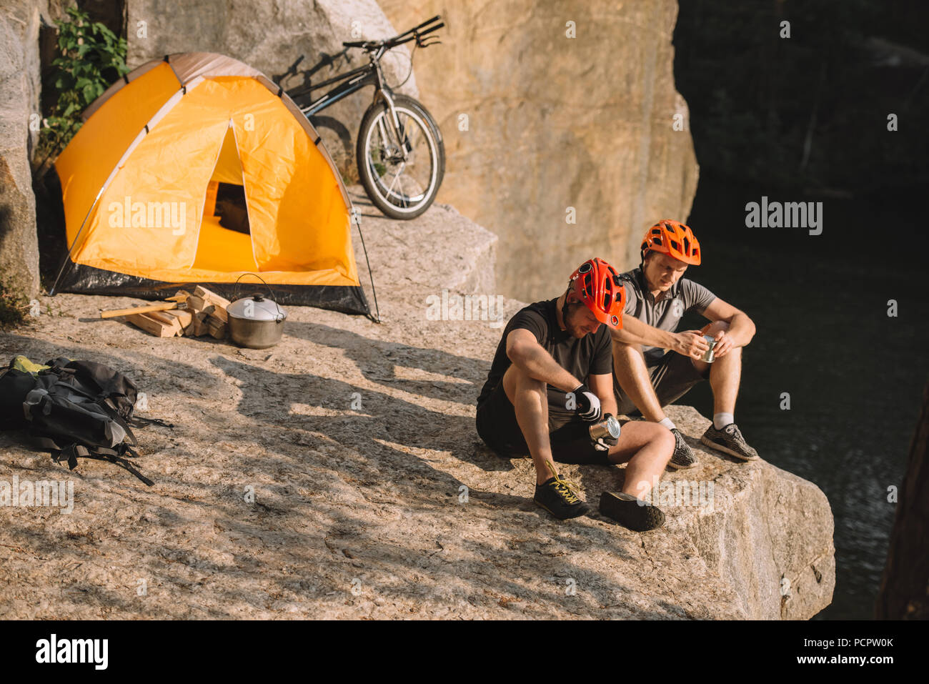 young bike travellers with canned food sitting on cliff - Stock Image