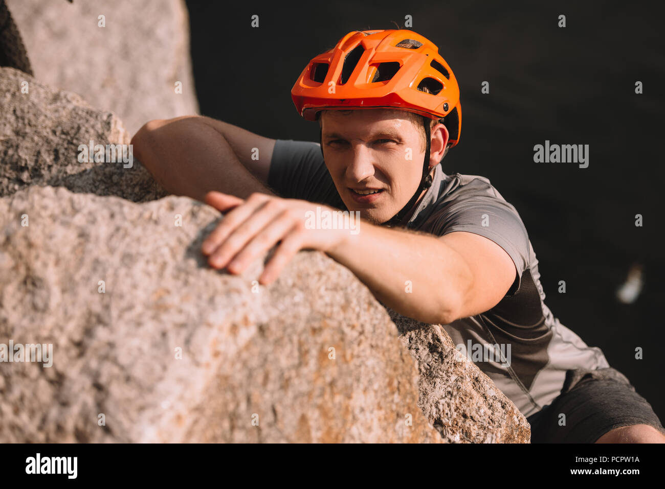 handsome young traveller in helmet climbing on rock and looking at camera - Stock Image