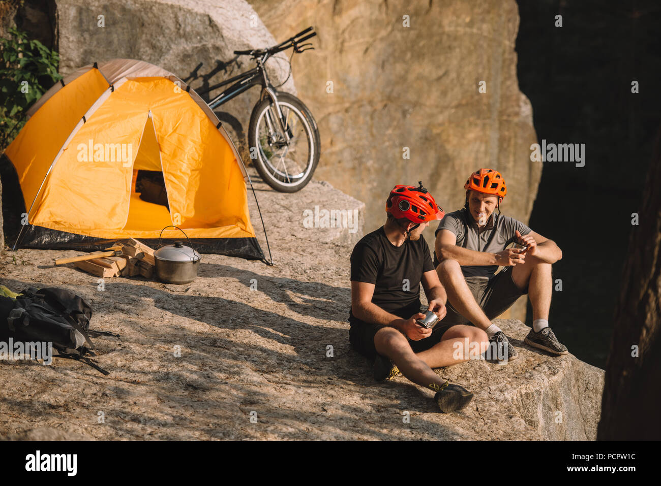 happy young bike travellers with canned food sitting on cliff - Stock Image