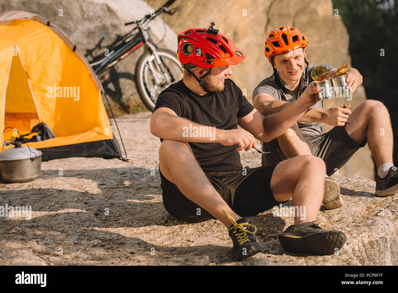 active travellers eating canned food on rocky cliff and clinking tins - Stock Image
