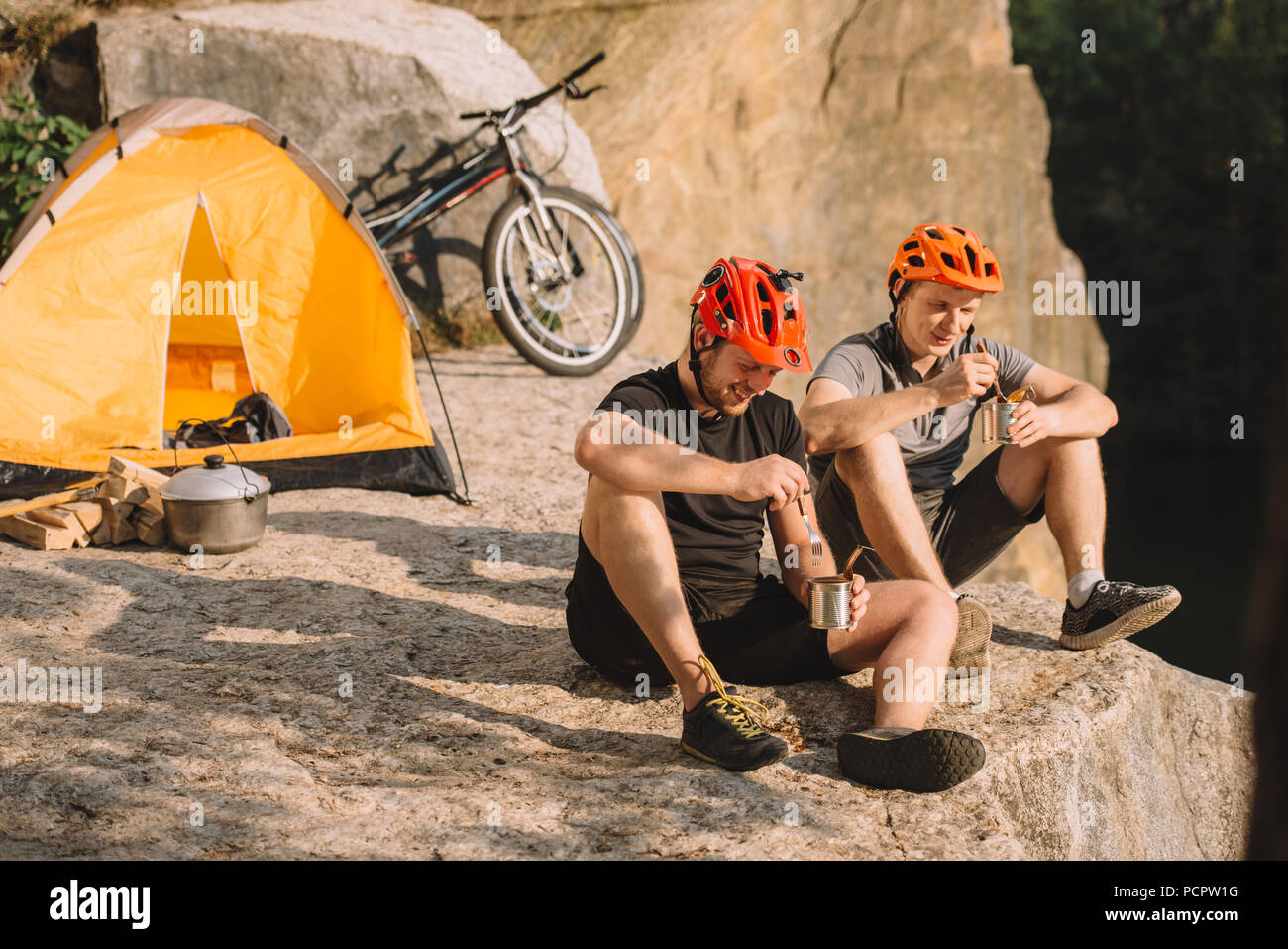 happy trial bikers eating canned food in camping on cliff - Stock Image