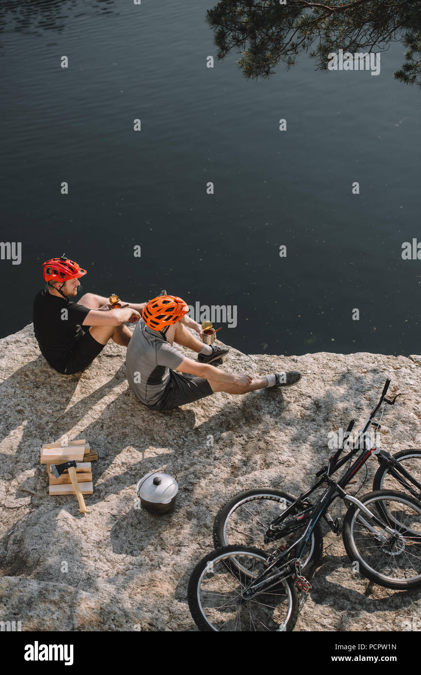 high angle view of young trial bikers eating canned food on rocky cliff - Stock Image