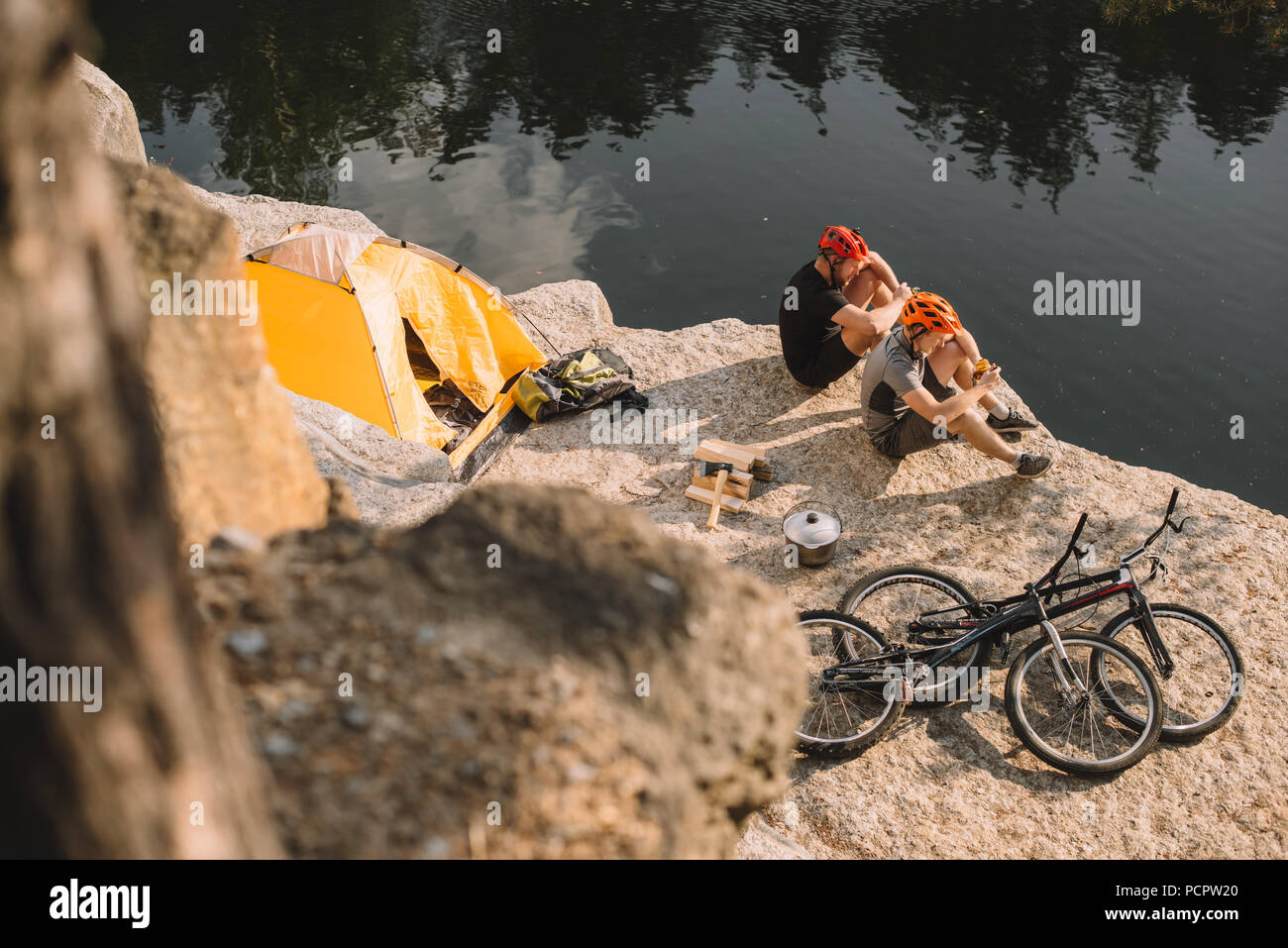 high angle view of active trial bikers eating canned food in camping on rocky cliff - Stock Image