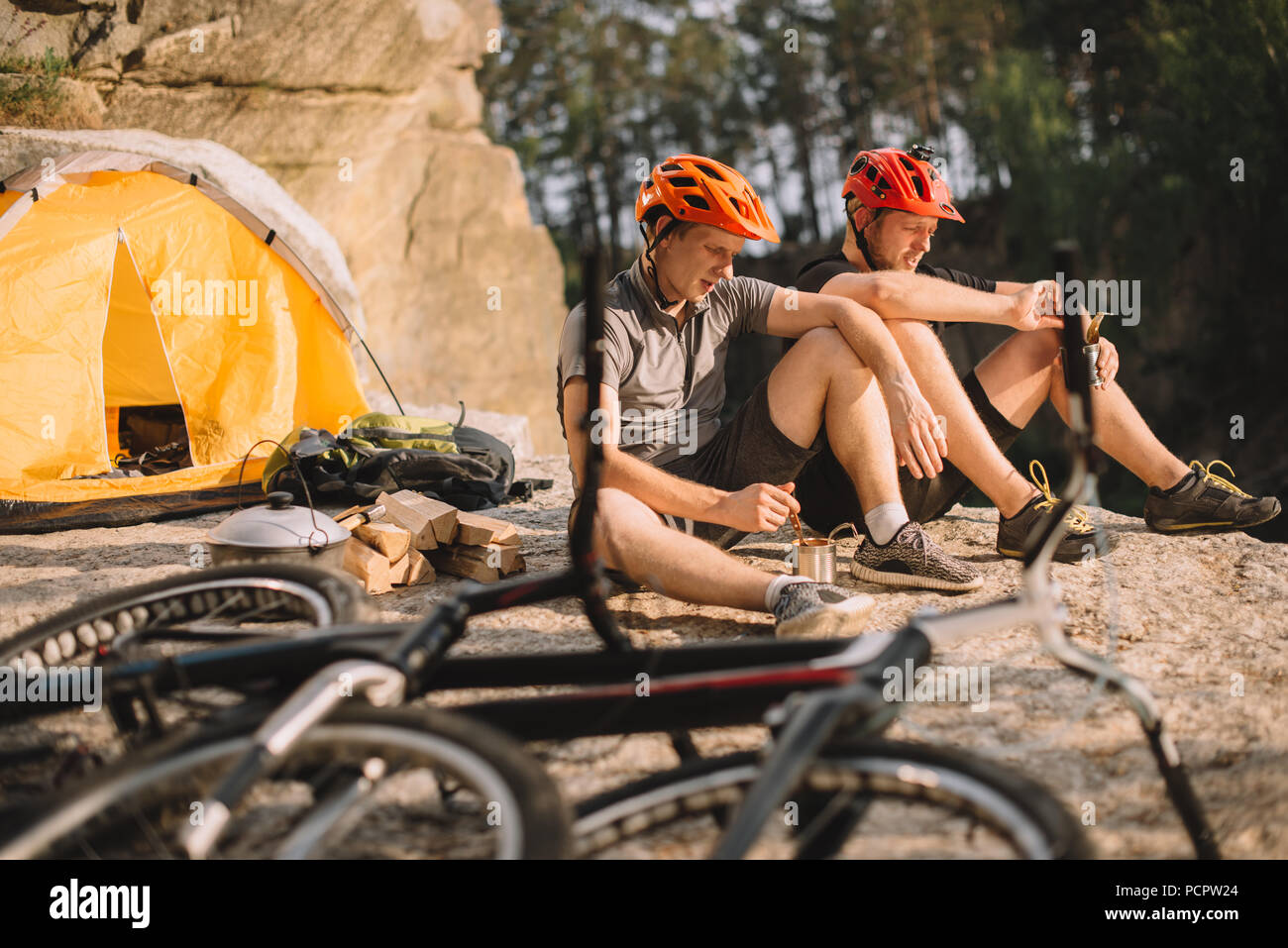young trial bikers eating canned food in camping outdoors - Stock Image