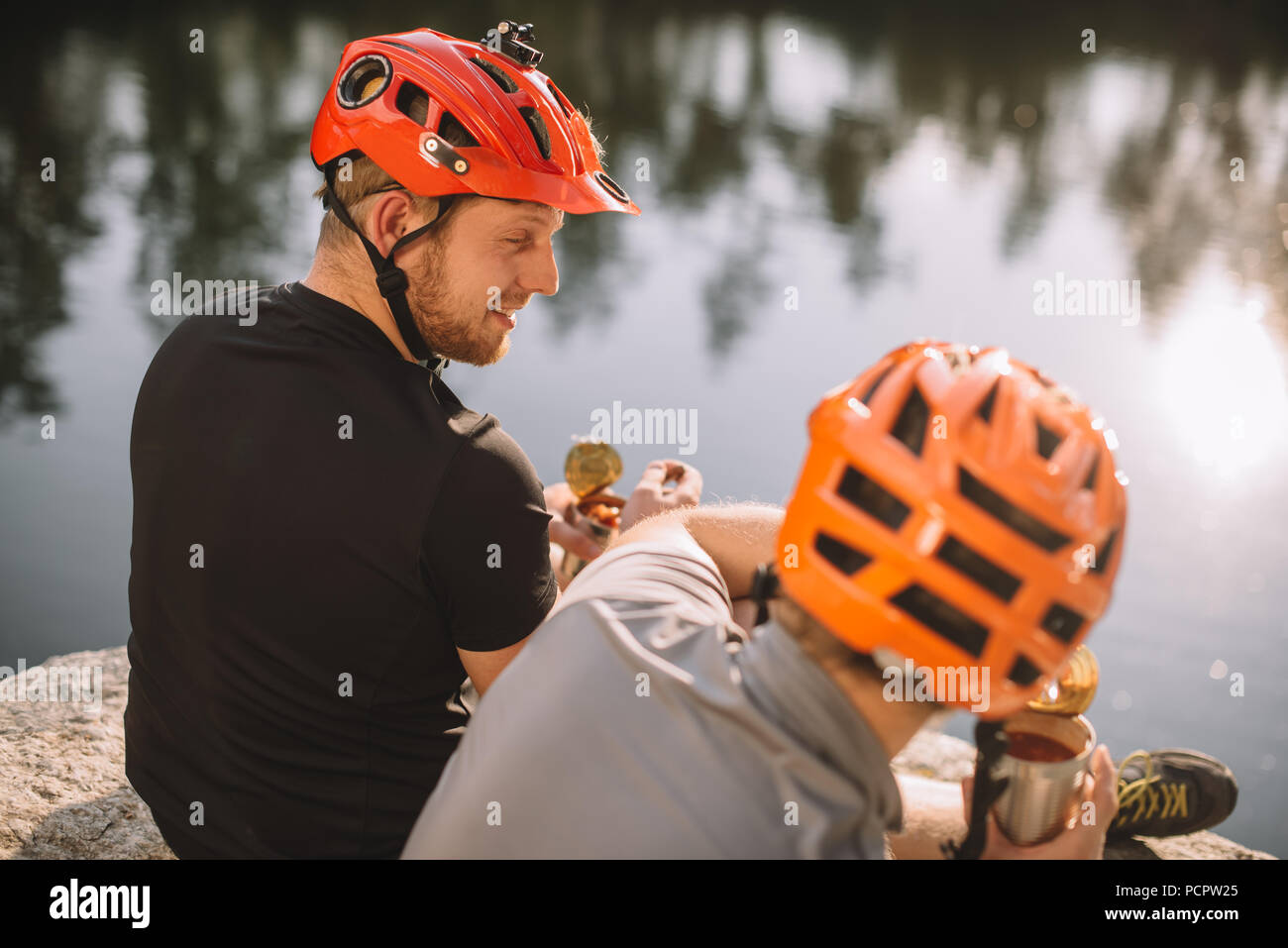 active young travellers eating canned food in camping in front of water surface - Stock Image