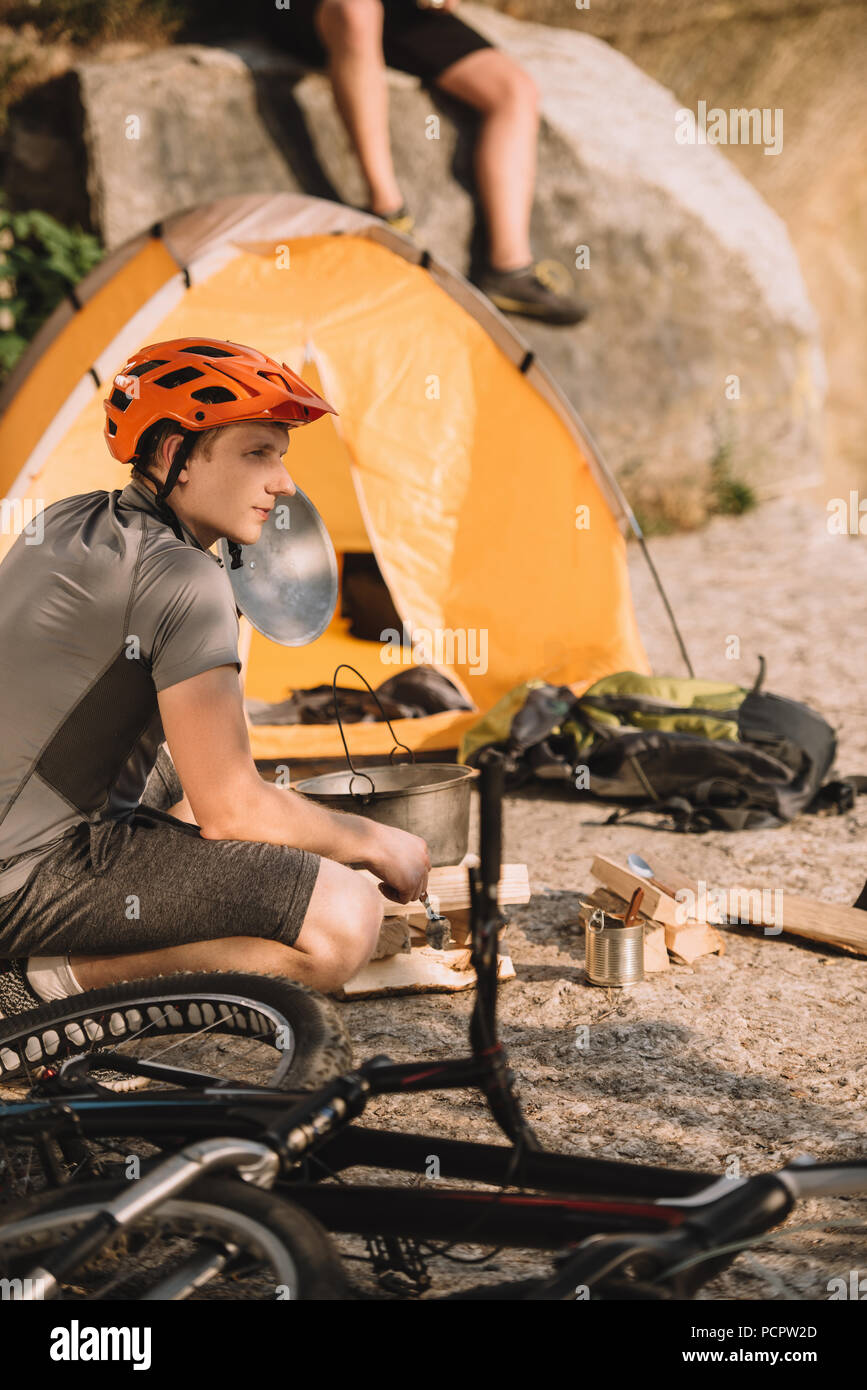 athletic young bike traveller sitting on rocks with camping tent and blurred friend sitting on background - Stock Image