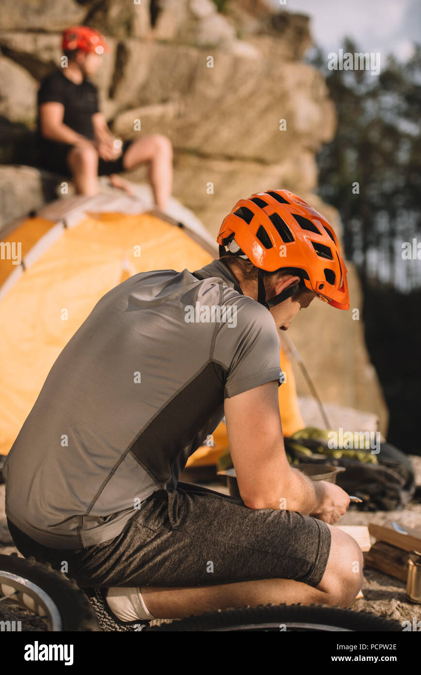 young bike traveller sitting on rocks with camping tent and blurred friend sitting on background - Stock Image