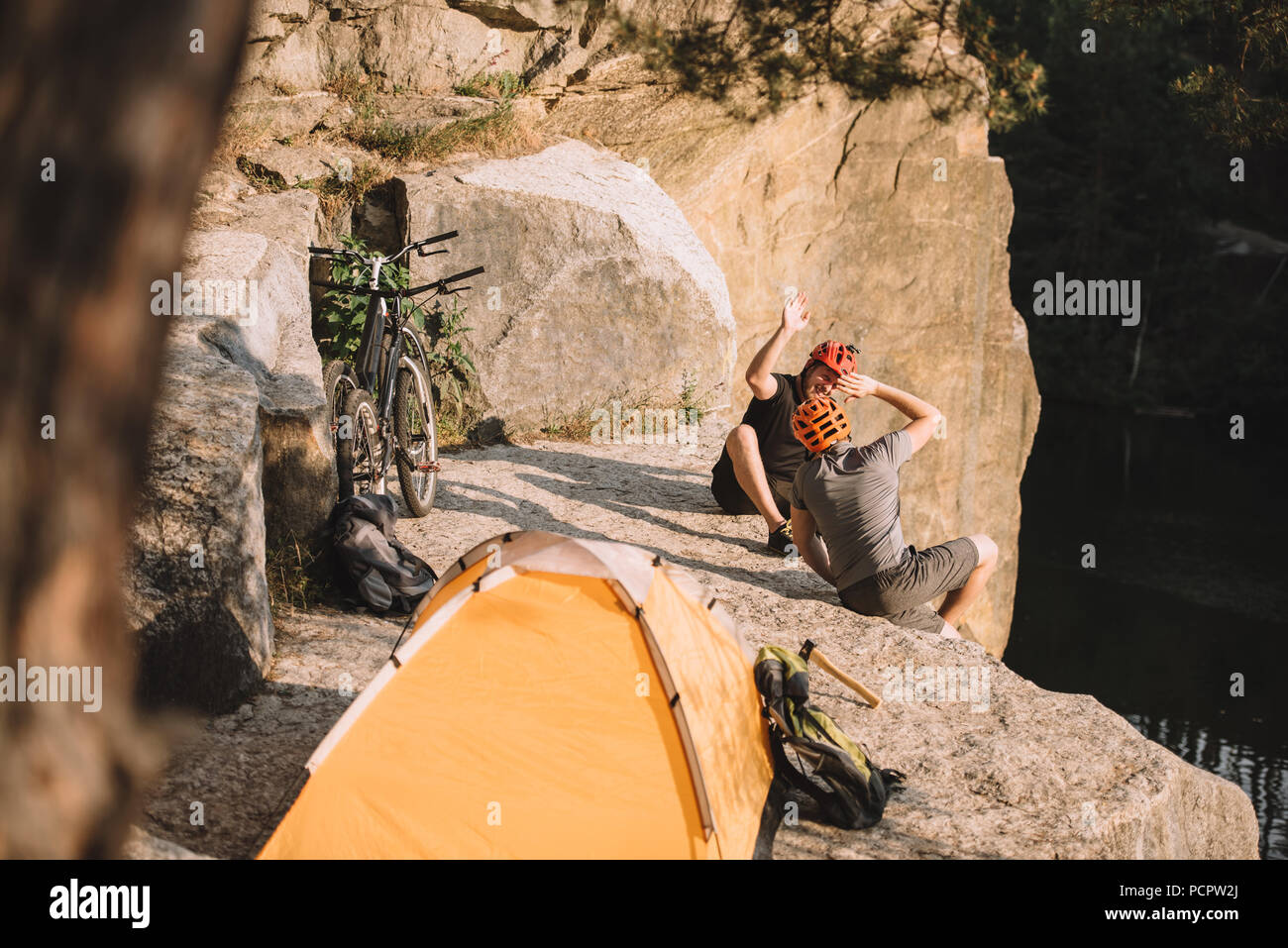 high angle view of active trial bikers sitting on rocky cliff with camping tent and giving high five - Stock Image