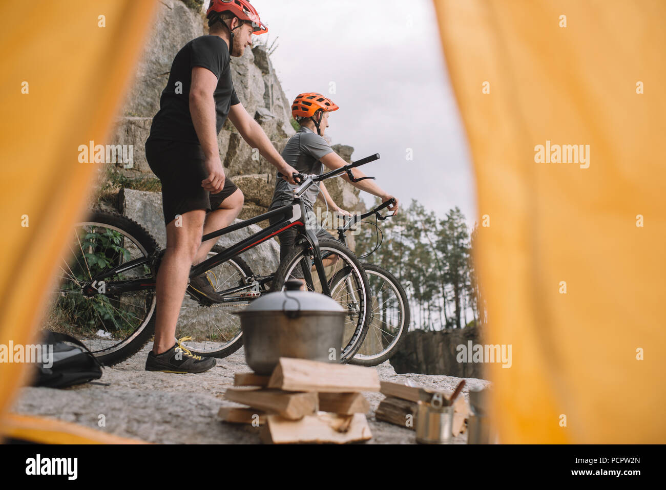 view of athletic trial bikers on rocky cliff outdoors from camping tent - Stock Image