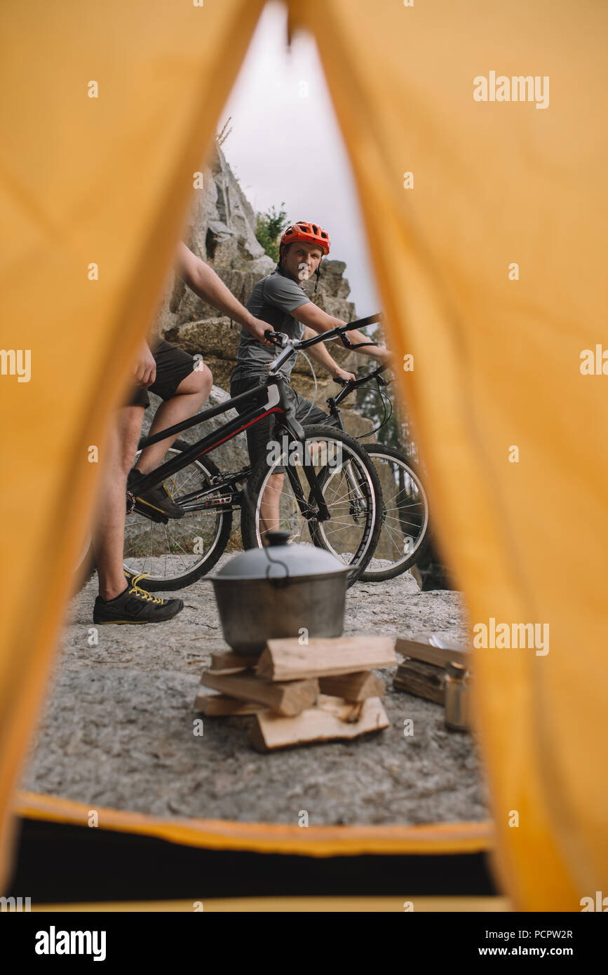 view of trial bikers on rocky cliff outdoors from camping tent - Stock Image