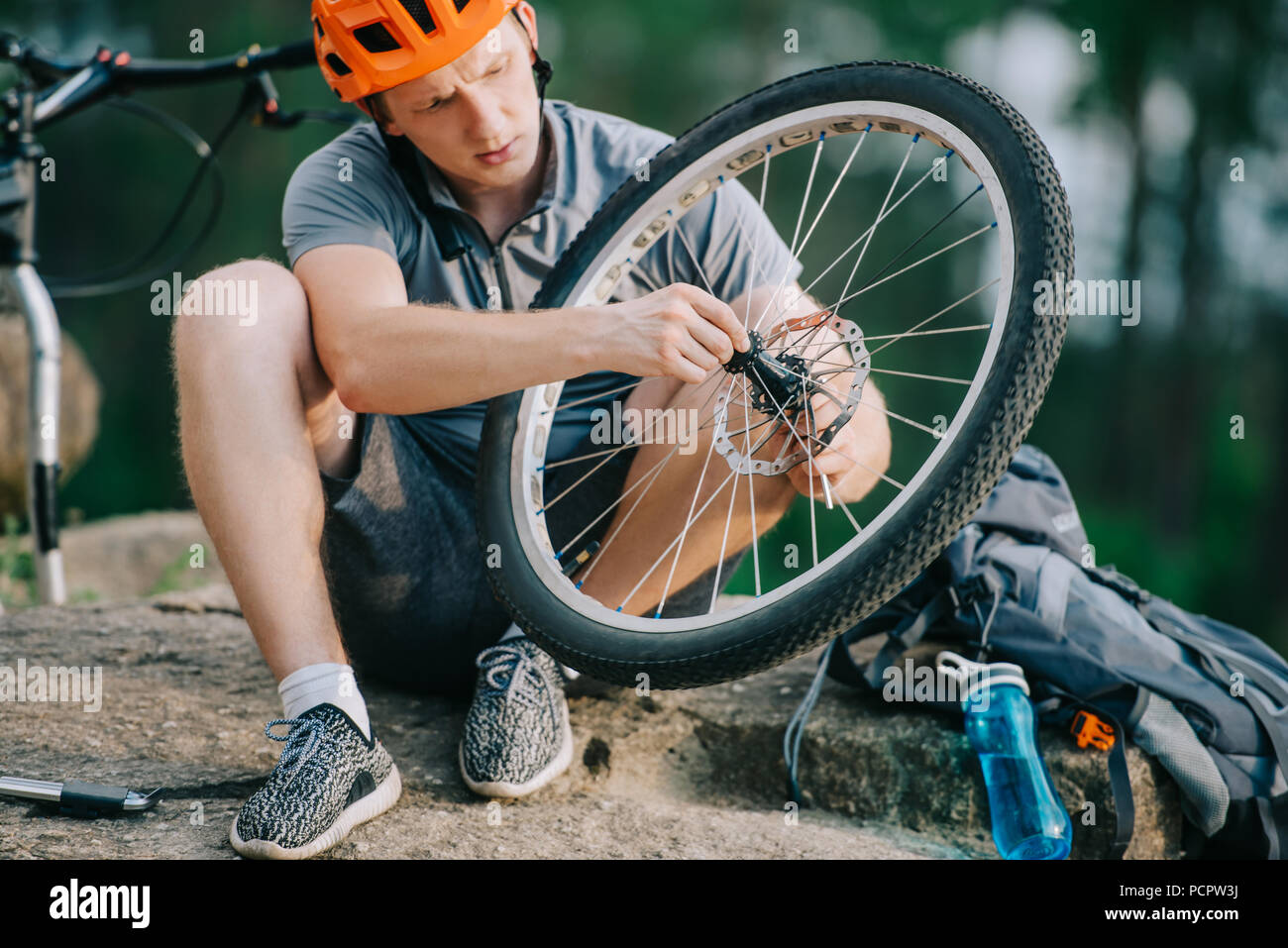 serious young trial biker fixing bicycle wheel outdoors while sitting on stone - Stock Image